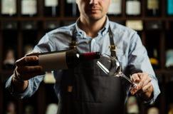 Sommelier masculin versant le vin rouge dans les verres à vin long-refoulés Image libre de droits