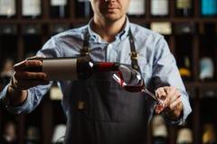 Sommelier masculin versant le vin rouge dans les verres à vin long-refoulés Photos libres de droits