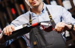 Sommelier masculin versant le vin rouge dans les verres à vin long-refoulés Photo libre de droits