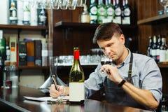 Sommelier masculino que prueba el vino rojo y que hace notas en el contador de la barra fotografía de archivo libre de regalías