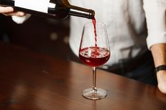 Sommelier masculino que vierte el vino rojo en las copas de tallo largo fotografía de archivo