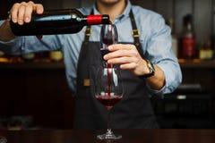 Sommelier masculino que vierte el vino rojo a través del aerador en el vidrio Fotografía de archivo libre de regalías