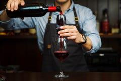 Sommelier masculino que vierte el vino rojo a través del aerador en el vidrio Foto de archivo