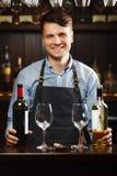 Sommelier med flaskor av rött och vitt vin och vinglas royaltyfri bild