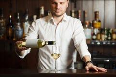 Sommelier no vinho branco de derramamento da camisa no vidro fotos de stock royalty free