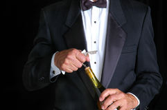Sommelier Opening Bottle of Wine. Sommelier in Tuxedo Opening a Bottle of Wine royalty free stock photos