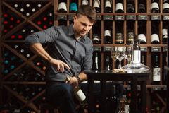 Sommelier opening white wine bottle with corckcrew. Sommelier male opening white wine glass bottle in cellar with containers of beverages of differents types and royalty free stock photo