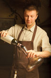 A sommelier opening wine bottle. A sommelier pouring red wine into decanter Royalty Free Stock Photography