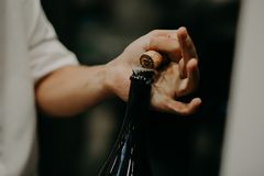Sommelier opening wine bottle in the wine cellar Royalty Free Stock Images