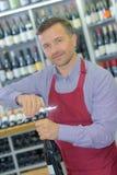 Sommelier opening wine bottle in wine cellar. Sommelier opening wine bottle in the wine cellar Royalty Free Stock Photo