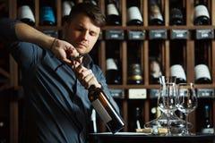 Sommelier ouvrant la bouteille de vin rouge avec le corckcrew images libres de droits