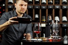 Sommelier pouring red wine from bottle in glass. Sommelier male pouring red wine from bottle having label into glass on angle, alcoholic beverage degustation stock photography