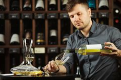 Sommelier pouring white wine from bottle in glass. Sommelier male pouring white wine from bottle having label into glass on angle, alcoholic beverage degustation royalty free stock photography