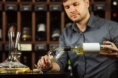 Sommelier pouring white wine from bottle in glass. Sommelier male pouring white wine from bottle having label into glass on angle, alcoholic beverage degustation royalty free stock photo