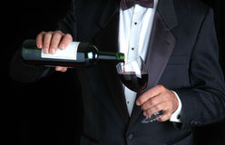 Sommelier Pouring Wine. Sommelier in Tuxedo Pouring Wine into a Wineglass royalty free stock image