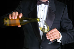 Sommelier Pouring Wine. Sommelier in Tuxedo Pouring White Wine from a Bottle into Wine Glass Royalty Free Stock Image