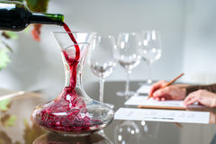 Sommelier pouring wine into decanter. Close up of Sommelier pouring red wine into decanter at wine tasting session royalty free stock image