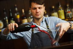 Sommelier pouring wine into glass from decanter. Male waiter. On background of bar counter with bottle of red wine Stock Photography