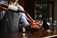 Sommelier pouring wine into glass from decanter. Male waiter. On background of bar counter with bottle of red wine Stock Images
