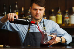 Sommelier pouring wine into glass from decanter. Male waiter. On background of bar counter with bottle of red wine Stock Photo
