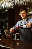 Sommelier pouring wine into glass from decanter. Male waiter. On background of bar counter with bottle of red wine Royalty Free Stock Image