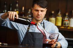 Sommelier pouring wine into glass from decanter. Male waiter. On background of bar counter with bottle of red wine Stock Image