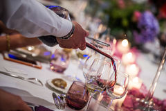 Sommelier pouring wine into glass from mixing bowl, luxury diner. Sommelier pouring wine into glass from mixing bowl at luxury diner Royalty Free Stock Photos