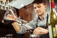 Sommelier pouring wine into glass from mixing bowl. Male waiter. Sommelier pouring wine into glass from decanter. Male waiter pour out alcohol beverage into Stock Photo