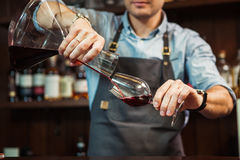 Sommelier pouring wine into glass from mixing bowl. Male waiter. Sommelier pouring wine into glass from decanter. Male waiter pour out alcohol beverage into Stock Photos