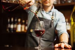 Sommelier pouring wine into glass from mixing bowl. Male waiter. Sommelier pouring wine into glass from decanter. Male waiter pour out alcohol beverage into Royalty Free Stock Image