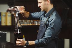 Sommelier pouring wine into glass from mixing bowl. Male waiter. Sommelier pouring wine into glass from decanter. Male waiter pour out alcohol beverage into Royalty Free Stock Photo