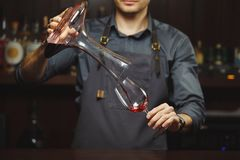 Sommelier pouring wine into glass from mixing bowl. Male waiter. Sommelier pouring wine into glass from decanter. Male waiter pour out alcohol beverage into Royalty Free Stock Photography
