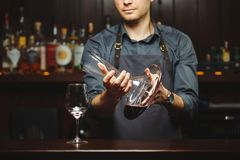 Sommelier pouring wine into glass from mixing bowl. Male waiter. Sommelier pouring wine into glass from decanter. Male waiter pour out alcohol beverage into Stock Image