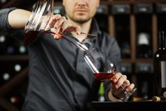 Sommelier pouring wine into glass from mixing bowl. Male waiter. Sommelier pouring wine into glass from decanter. Male waiter pour out alcohol beverage into Stock Images