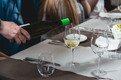 Sommelier pouring wine into glass at wine and food tasting. A lot of different wine glasses on the table at wine tasting. sommelier at wine tasting talks about Royalty Free Stock Images