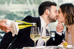 Sommelier pouring wine with kissing couple in background. Stock Photography