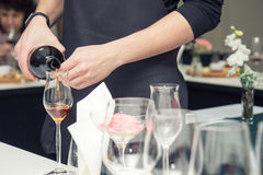 Sommelier pouring wine to the wine glass. Sommelier pouring rose wine to the wine glass. Serving table prepared for event party or wedding. Soft focus, selective Royalty Free Stock Photography