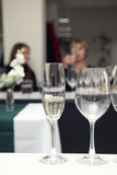 Sommelier pouring wine to the wine glass. Sparkling wine to the wine glass. Serving table prepared for event party or wedding. Soft focus, selective focus. Toned royalty free stock photography