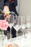 Sommelier pouring wine to the wine glass. Sommelier pouring white wine to the wine glass. Serving table prepared for event party or wedding. Soft focus Royalty Free Stock Photo