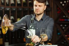 Sommelier pours white wine from decanter to the glass. Sommelier pouring previously decants white wine beverage from special mixing container into transparent stock photo