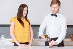 Sommelier pours wine into glass. Wine degustation. Sommelier wearing a bow tie pouring wine to the glass and young attractive women looking at this smiling Stock Images
