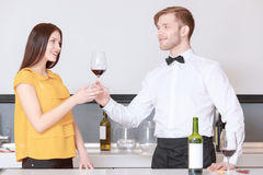 Sommelier pours wine into glass. Taste of the best wine. Young handsome sommelier in a bow tie giving a glass with red wine to a beautiful women at degustation Stock Photos