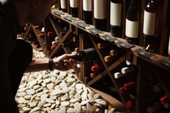 Sommelier prenant une de bouteilles de cave en bois photographie stock