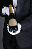 Sommelier Presenting Champagne Bottle. Closeup of a Sommelier in a tuxedo presenting a champagne bottle, Vertical format over a light to dark gray background Stock Photos