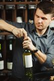 Sommelier in process of opening white wine bottle. Sommelier in process of opening bottle of white white, container having label on it, man wearing modern watch stock photo