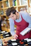 Sommelier professionnel beau choisissant le vin de bouteille Image stock