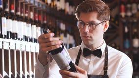 Sommelier que presenta la botella de vino tinto al cliente en una bodega almacen de video