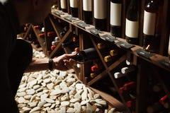 Sommelier que toma una de botellas del sótano de madera fotografía de archivo