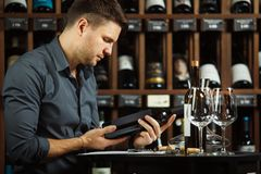Sommelier reading label of wine bottle in hands. Sommelier male reading label of wine bottle holding in hands, man learning information about alcoholic product stock images