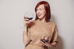 Sommelier redhaired alegre novo da menina no sorriso, nas piscadelas e na posse brancos do fundo com dois vidros do vinho tinto T imagem de stock royalty free